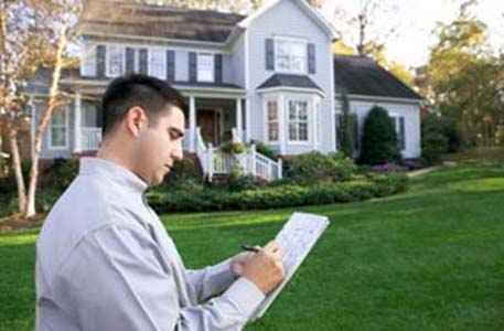 Investor with clipboard in front yard copy